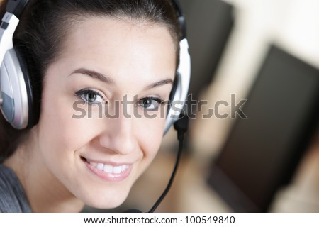 Cute business customer service woman smiling, computer on foreground - stock photo