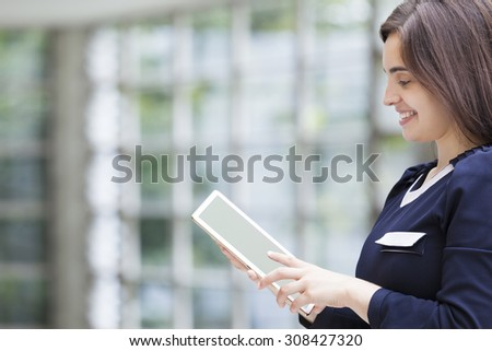 Cute business woman holding a tablet computer at the office