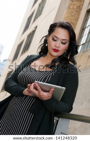 Cute business woman on tablet computer on High Line, NYC - stock photo