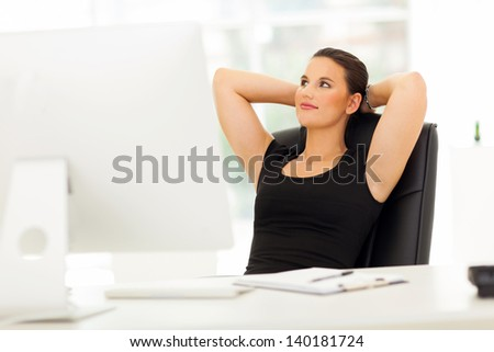 cute businesswoman daydreaming in office with hand behind her head