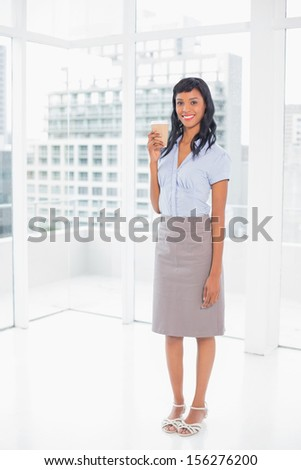 Cute businesswoman holding a coffee in office - stock photo