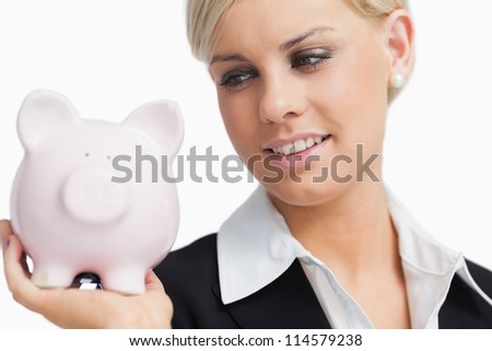 Cute businesswoman holding a piggy-bank against white background - stock photo