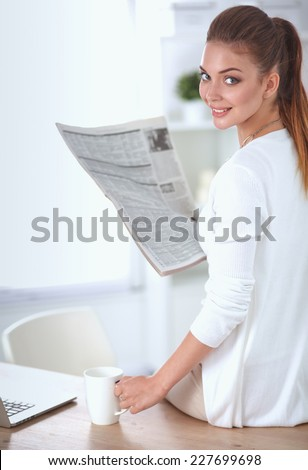 Cute businesswoman holding newspaper sitting at her desk in office - stock photo