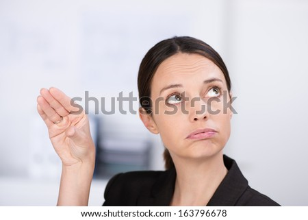 Cute businesswoman pursing her lips making a gesture with her hand to show an approximate amount while looking up thoughtfully - stock photo