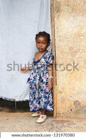 Cute but serious little black African girl in pink sunday dress next to her home door made of fabric; third world or developing country concept. - stock photo