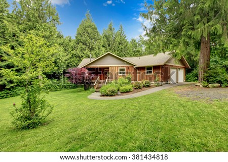 cute cabin house with large grassy yard.