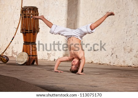 Cute capoeria boy in headstand with African music instruments - stock photo