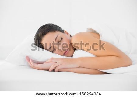 Cute casual brunette sleeping in her bed in bright bedroom - stock photo