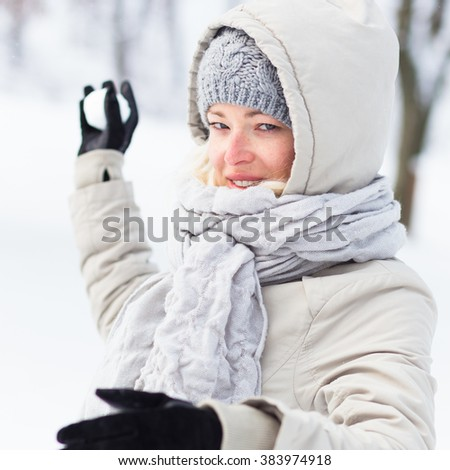 Cute casual young woman snowball fighting in winter time. - stock photo