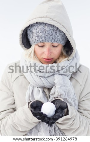 Cute casual young woman wearing glooves, woolen cap and scarf, holding icy snowball in cold winter time. Lady looking down at snowball. - stock photo