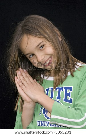 cute caucasian american girl clasping hands together as if praying on black