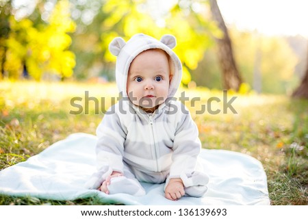 Cute caucasian baby boy in park looks at camera