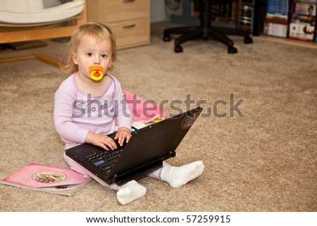 Cute Caucasian baby girl playing with black laptop computer. - stock photo