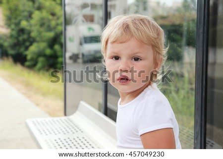 Cute Caucasian blond baby girl waits on a bus stop - stock photo
