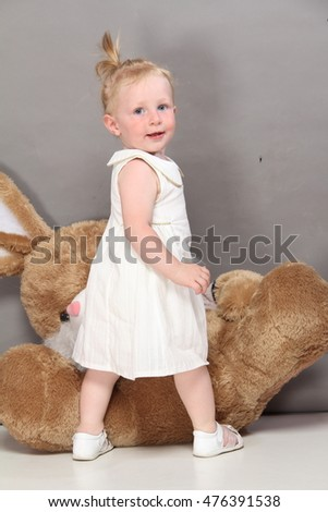cute caucasian blonde blue eyed girl in white dress playing, studio photo