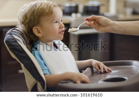 Cute caucasian boy being fed by his mom