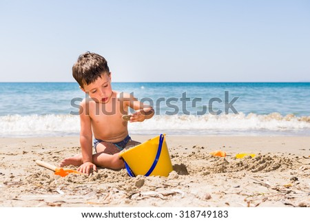 cute caucasian child playing on the beach with pail and shovel in a sunny day with sea background