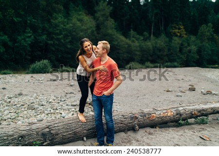cute caucasian couple next to sandy river standing on log laughing