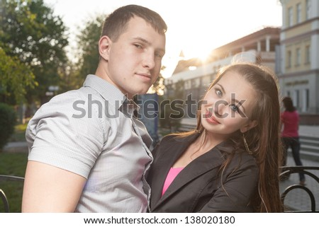 Cute Caucasian couple pose for the camera outdoors with town on background - stock photo