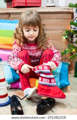Cute Caucasian girl wearing the red fur boots, Christmas eve - stock photo
