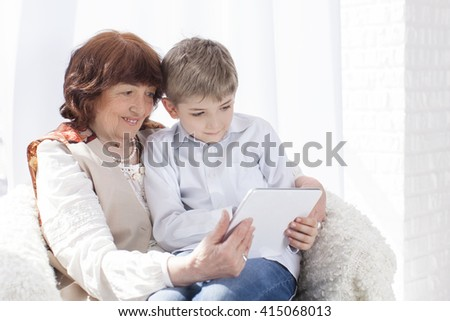 Cute Caucasian grandmother and grandson sitting in armchair and look at the tablet. Horizontal color image. Light background.