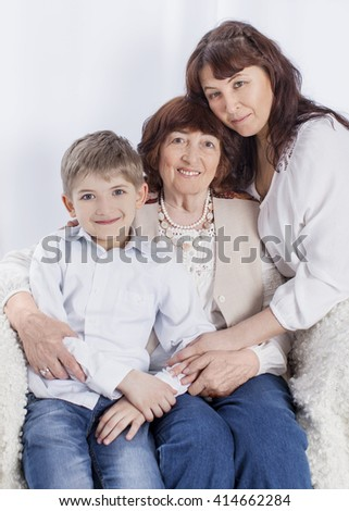 Cute caucasian grandmother, mother and grandson. Family portrait on the chair. Vertical color image. Light background - stock photo