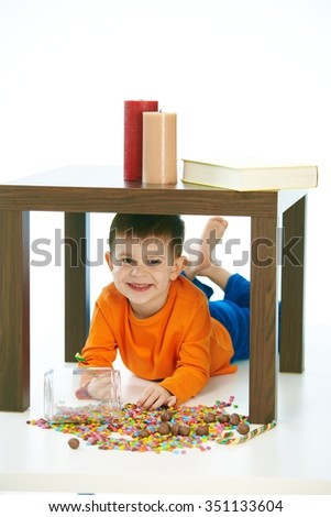 Cute caucasian kid lying under table with sweets jar spilled. Happy, smiling, isolated on white. - stock photo