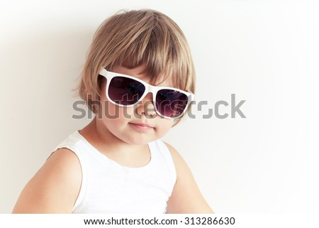 Cute Caucasian little girl in sunglasses on white wall background, closeup studio portrait - stock photo