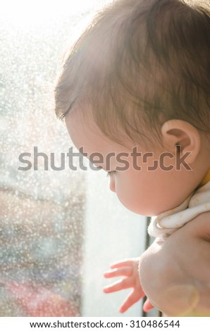 Cute caucasian little newborn baby girl sitting on mother's hands and looking at window with beautiful brown eyes. Selective focus and highlights make special effect and show the concept of childhood. - stock photo