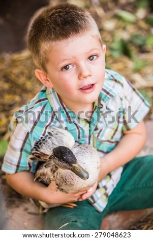 Cute Caucasian male child with duck his pet duck
