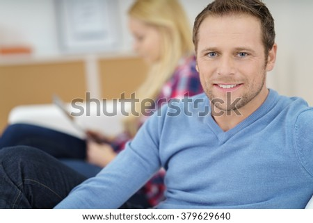 Cute Caucasian man in blue shirt with stubble relaxing on sofa with blond woman in background - stock photo