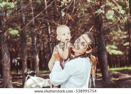 Cute caucasian mother holding her newborn baby outdoor in the woods