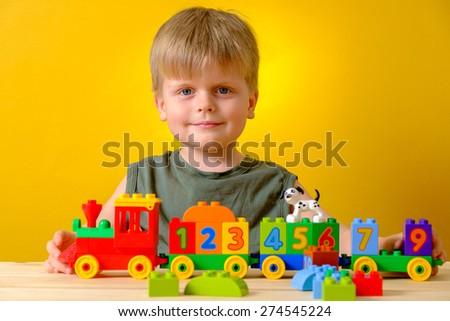 Cute caucasian preschooler boy playing with bricks. - stock photo