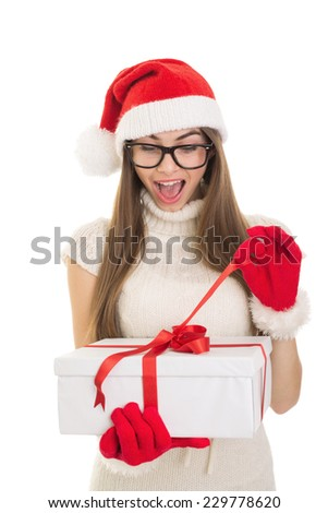 Cute Caucasian Santa teenage girl with eyeglasses opening Christmas present. Pretty young surprised woman unwrapping gift box. Isolated on white background. No retouch. - stock photo