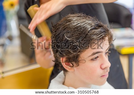 Cute caucasian teenage boy sitting at the hairdresser salon for a haircut