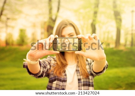 Cute Caucasian teenage girl taking a selfie with smartphone in park. Beautiful modern hipster young woman in checkered shirt taking a self portrait with phone. - stock photo