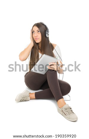 Cute Caucasian teenage girl with headphones listening music on tablet sitting. Isolated on white background. Model looking up and holding headphones.