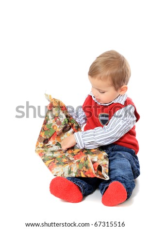 Cute caucasian toddler unwrapping christmas gift. All isolated on white background.