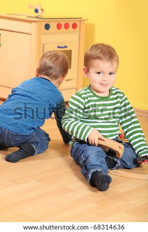 Cute caucasian toddlers playing fun in kindergarten.