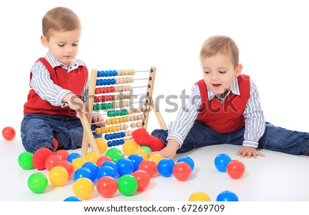 Cute caucasian twin brothers playing with toys. All isolated on white background. Foreground in very light grey.