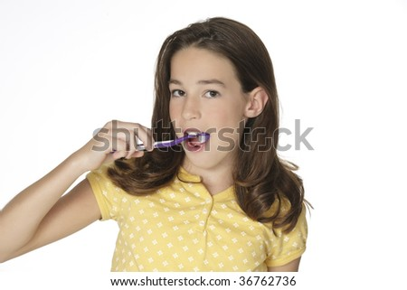 Cute Caucasion girl brushing her teeth isolated on a white background - stock photo
