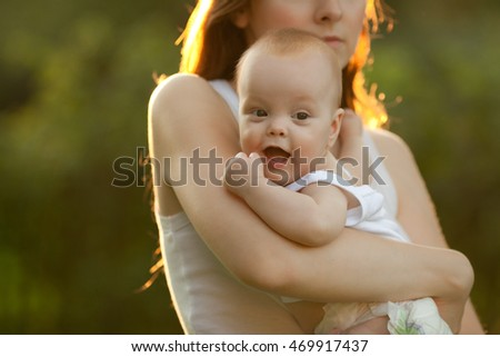 Cute cheerful baby on mother's hands