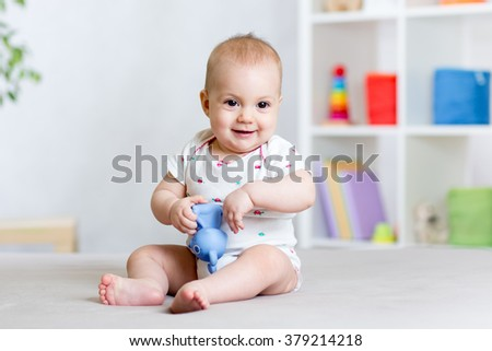 cute cheerful baby playing with toy at home - stock photo