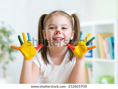 cute cheerful child girl showing her hands painted in bright colors - stock photo