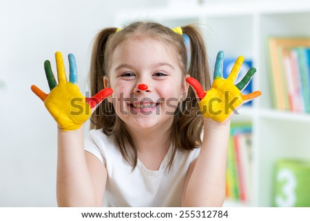 cute cheerful child girl with painted hands and face - stock photo