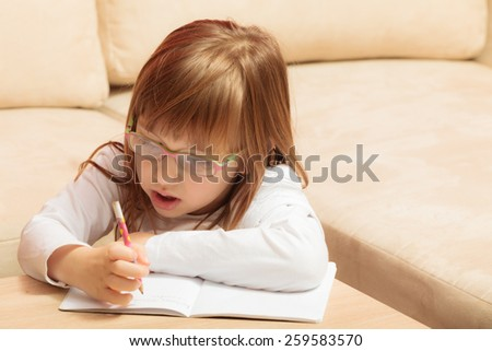 Cute cheerful child little girl drawing writing in notebook using pen while laying on couch at home