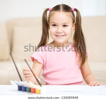 Cute cheerful child play with paints while sitting at table - stock photo