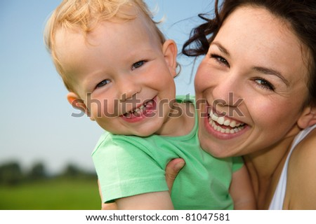 Cute cheerful child with mother play outdoors - stock photo