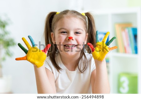 cute cheerful kid with painted hands and face - stock photo
