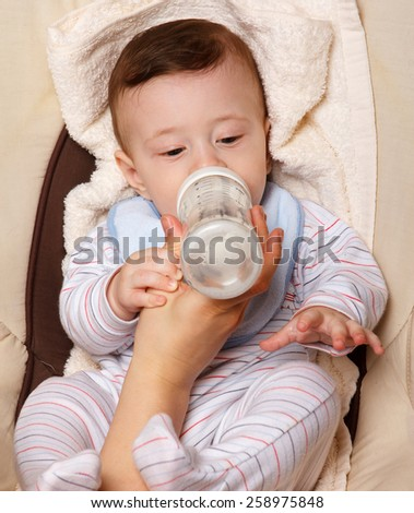 Cute cheerful  little baby boy eating. - stock photo